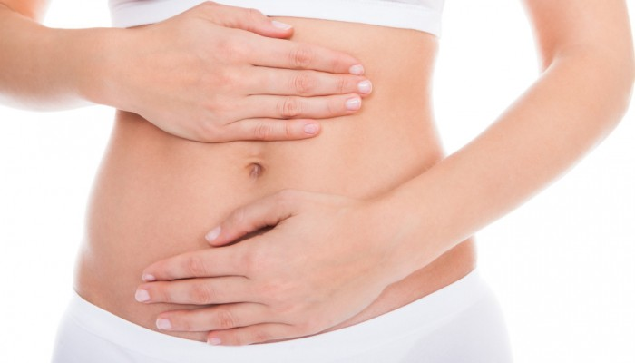 Young Woman With Pain In Her Stomach Isolated Over White Background