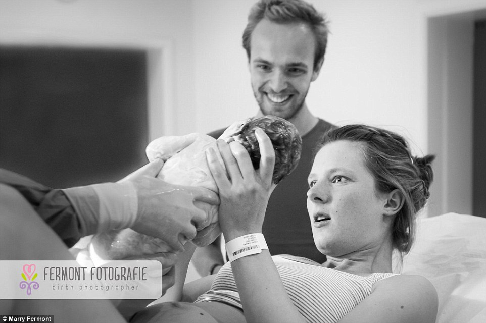 A mother looks amazed as she meets her baby for the very first time. Marry often photographs women giving birth but says the shoot would not be complete without capturing birth session the first emotion when the baby is born